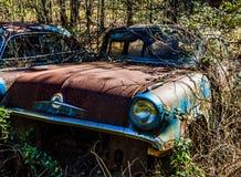 Rostig, gammal kastad bil i träna Royaltyfri Fotografi
