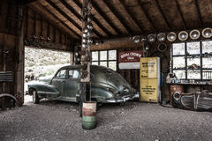 Rostig gammal tappningbil i övergett mekanikergarage Royaltyfri Foto