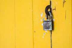 rostig hänglås på tappninggulingdörr Royaltyfri Foto