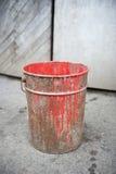 Rostig hink av röd målarfärg Arkivfoto