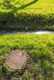 Rostig ist die Abwasserkanalluke und -gosse mit Wasser im Park Stockbild