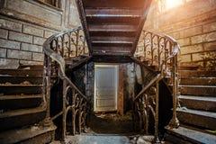 Rostig järntappningtrappa med nitar i den gamla övergav herrgården Royaltyfri Fotografi