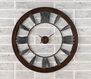Rostig klocka som hänger på den vita tegelstenväggen Royaltyfri Foto