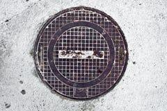Rostig manhålräkning för metall i betong arkivfoton