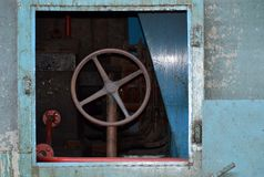 Rostig metall rullar in en gammal fabrik med en turkosyttersida royaltyfri fotografi