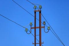 Rostig metallkraftledningservice med trådar och närbild för glass isolatorer mot den blåa himlen arkivbilder