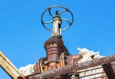 Rostig rörledning med ventiler mot bakgrunden för blå himmel Royaltyfri Foto