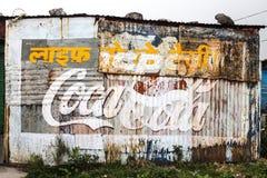 Rostig sjaskig vägg med Pepsi och coca - colahanden målade annonseringen royaltyfri bild