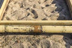 Rostig stång på sanden av en strand Royaltyfri Foto