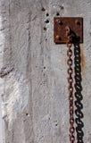 Rostig stark kedja som hänger längs väggen Royaltyfri Foto