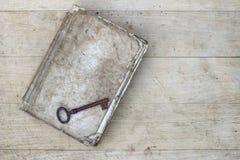 Rostig tangent på den gamla sönderslitna boken Arkivfoton