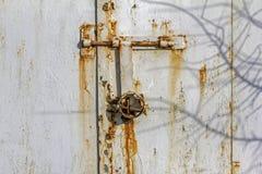 Rostig vägg av en metallkoja med anfrätta bultar och hänglåset Royaltyfri Bild