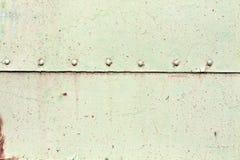 Rostig yttersida för metallplatta med nitar Arkivbilder