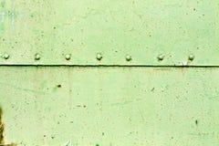Rostig yttersida för metallplatta med nitar Arkivfoton