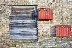 Rostiga brevlådor på tegelstengrungeväggen Arkivbild