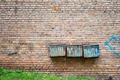 Rostiga brevlådor på tegelstengrungeväggen Arkivfoto