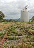 Rostiga gamla järnvägsspår och vetesilo royaltyfria bilder