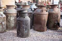Rostiga gamla mjölkar cans på en loppmarknad Arkivbilder