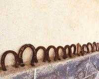 Rostiga hästskor på väggen samlat begrepp för bra lycka hoppas royaltyfri fotografi