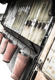 Rostiga hinkar som hänger från rostigt skjul Arkivbild