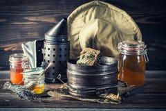 Rostiga hjälpmedel för biodling med ny och söt honung Arkivfoton