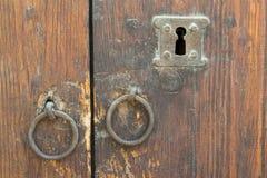 Rostiga järnringdörrknoppar och nyckelhål över en gammal trägrungedörr Royaltyfri Fotografi
