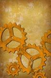 Rostiga kugghjul mot en fläckig gulaktig bakgrund Arkivbild