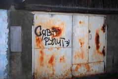 Rostiga metalldörrar med grafitti royaltyfria foton