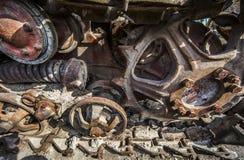 Rostiga och smutsiga spår och kugghjul av en gammal traktor på skrotupplaget Royaltyfri Fotografi