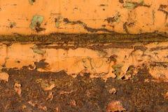 Rostiga skrapor på orange målat stål royaltyfria bilder