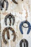 Rostiga uppochnervända hästskor på den wood panelen Royaltyfria Foton