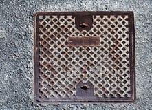 Rostige Abwasserkanalkappe auf Betondecke Stockbilder