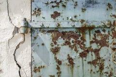 Rostige alte blaue Tür mit gebrochenem Wand-, abstraktem und strukturiertemhintergrund Lizenzfreies Stockbild