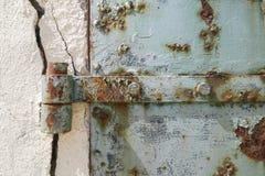 Rostige alte blaue Tür mit gebrochenem Wand-, abstraktem und strukturiertemhintergrund Lizenzfreies Stockfoto