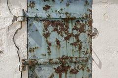Rostige alte blaue Tür mit gebrochenem Wand-, abstraktem und strukturiertemhintergrund Lizenzfreie Stockfotos
