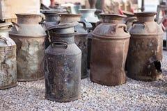 Rostige alte Milchdosen an einer Flohmarkt Stockbilder