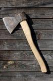 Rostige Axt des traditionellen Eisens mit Holzgriff auf hölzernem Planke wa lizenzfreie stockfotos