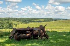 Rostige Ballenpresse mit Rolling Hills im Hintergrund Stockfoto