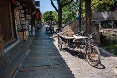Rostige drei drehten das elektrische Fahrrad der Fracht, das auf Kanaldamm geparkt wurde Stockbilder