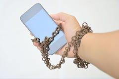Rostige Eisenkette, die Hand und intelligentes Telefon zusammen bindet stockfotos