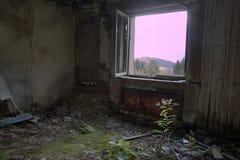 Rostige Heizung und Gras in einem alten Herbergesraum Stockbild
