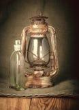 Rostige Lampe und eine Flasche Kerosin Lizenzfreies Stockfoto