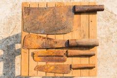 Rostige Messer auf hölzernen Fliesen, Landwirtausrüstung in Thailand Lizenzfreie Stockbilder