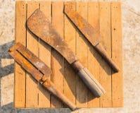 Rostige Messer auf hölzernen Fliesen, Landwirtausrüstung in Thailand Stockfotos