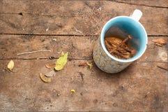 Rostige Nägel in einem Tasse Kaffee auf dem Bretterboden Lizenzfreie Stockfotografie