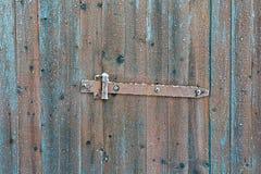 Rostige Sperrschieberklinke auf gefrorener hölzerner alter Tür im Winter Stockbilder