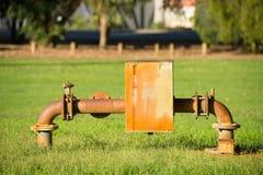 Rostige Stromversorgungspumpenrohrleitung im Park Lizenzfreie Stockfotos