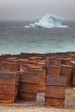 Rostige Trommeln auf arktischer Küste mit Eisberg auf Hintergrund Stockbild
