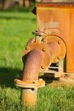 Rostige Versorgungspumpenrohrleitung auf grünem Gras Lizenzfreie Stockfotos