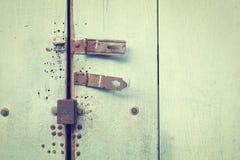 Rostiger Bolzen auf blauer Holztür Stockbilder